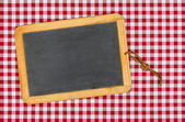 Empty blackboard with chalk on a red checkered table cloth — Stock Photo
