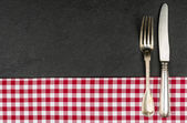 Silverware on a slate plate with a red checkered tablecloth — Stock Photo