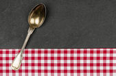 Silver spoon on a slate plate with a red checkered tablecloth — Stock Photo