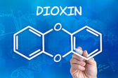 Hand with pen drawing the chemical formula of dioxin — Zdjęcie stockowe