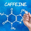 Hand with pen drawing chemical formulof Caffeine — Stock Photo #29122421