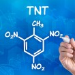 Stock Photo: Hand with pen drawing chemical formulof TNT