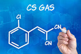 Hand with pen drawing the chemical formula of CS Gas — Стоковое фото