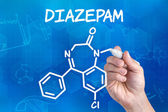 Hand with pen drawing the chemical formula of Diazepam — Stock Photo
