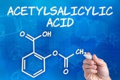 Hand with pen drawing the chemical formula of acetylsalicylic acid — Stock Photo