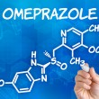 Hand with pen drawing the chemical formula of omeprazole — Стоковая фотография