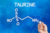 Hand with pen drawing the chemical formula of taurine — Stock Photo