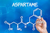 アスパルテームの化学式の描画ペンを持つ手します。 — ストック写真