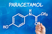 Hand with pen drawing the chemical formula of paracetamol — Stock Photo