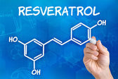 Hand with pen drawing the chemical formula of resveratrol — Stock Photo