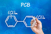Hand with pen drawing the chemical formula of PCB — Stock Photo