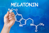 Hand with pen drawing the chemical formula of melatonin — Stock Photo
