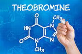Hand with pen drawing the chemical formula of theobromine — Stock Photo