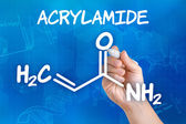 Hand with pen drawing the chemical formula of acrylamide — Stock Photo