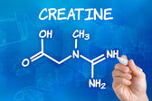 Hand with pen drawing the chemical formula of creatine — 图库照片