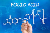 Hand with pen drawing the chemical formula of folic acid — 图库照片
