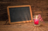 Candle in front of a blank chalkboard — Stock Photo