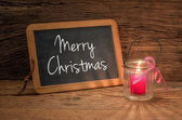 Candle in front of a chalkboard with the text Merry Christmas — Stock Photo