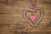 Rustic wooden background with a braided heart — Stock Photo