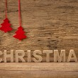 Word christmas in front of rustic background — Stock Photo #37062601