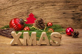 The word xmas in front of a rustic background — Stock Photo