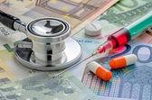 Stethoscope and syringe on bills — Stock Photo