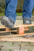 Worker with safety boots steps on a nail — Stok fotoğraf