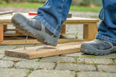Worker with safety boots steps on a nail — Стоковое фото