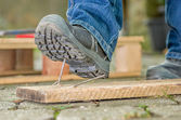 Worker with safety boots steps on a nail — 图库照片