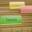 Hanging file folder labeled with Taxes — Stock Photo #38432247