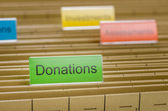 Hanging file folder labeled with Donations — Stock Photo