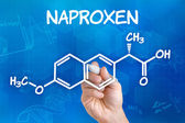 Hand with pen drawing the chemical formula of naproxen — Stock Photo