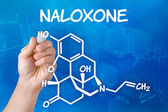 Hand with pen drawing the chemical formula of naloxone — Stock Photo