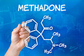 Hand with pen drawing the chemical formula of methadone — 图库照片