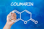 Hand with pen drawing the chemical formula of coumarin — 图库照片