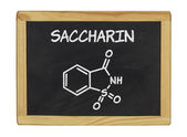 Chemical formula of saccharin on a blackboard — Stock Photo
