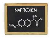 Chemical formula of naproxen on a blackboard — Stock Photo