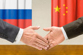 Representatives of Russia and China shake hands — Stock Photo