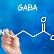 Hand with pen drawing the chemical formula of GABA — Stock Photo #48035021