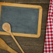 Empty blackboard with wooden spoons and red checkered tablecloth — Stock Photo #48253831