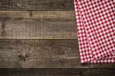 Rustic wooden boards with a red checkered tablecloth — Stock Photo