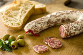 Salami with baguette and green olives — Stock Photo