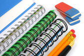 Notebooks, pencils, erasers and pen — Stock Photo
