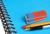 Pen, pencil and erasers on a notebook — Stock Photo