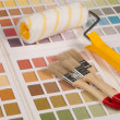 Brushes and a paint roller on color palette — Stock Photo