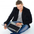 Smiling young man working at laptop — Stock Photo