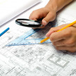 Man working with pencil and a magnifier on blueprints — Stock Photo