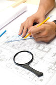 Man working with pencil and a square drawing on blueprints — Stock Photo