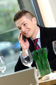 Young business man talking on the phone during lunch time — Stock Photo