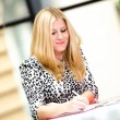 Blonde business woman standing and writing — Stock Photo #16217249